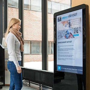 Woman in front of digital screen to display Digital signage ROI